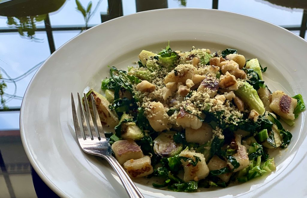 Pan-seared vegan google chef gnocchi with kale, Brussels sprouts, toasted walnuts and garlic shake adapted from Charlie Ayers Food Network Recipe