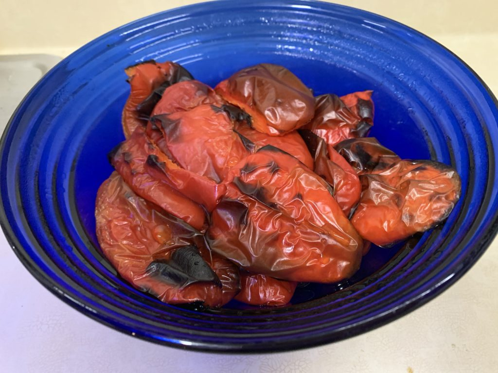 Steamed, roasted red peppers in a blue bowl ready to peel off the blistered skins.