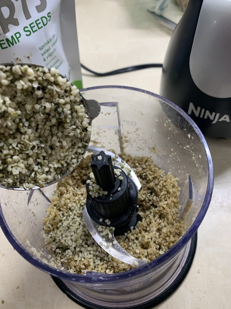 adding the remaining hemp seeds to the vegan hemp seed parm in a small food processor