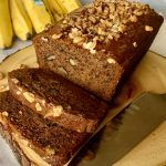 sliced banana bread on a wooden cutting board with a big knife