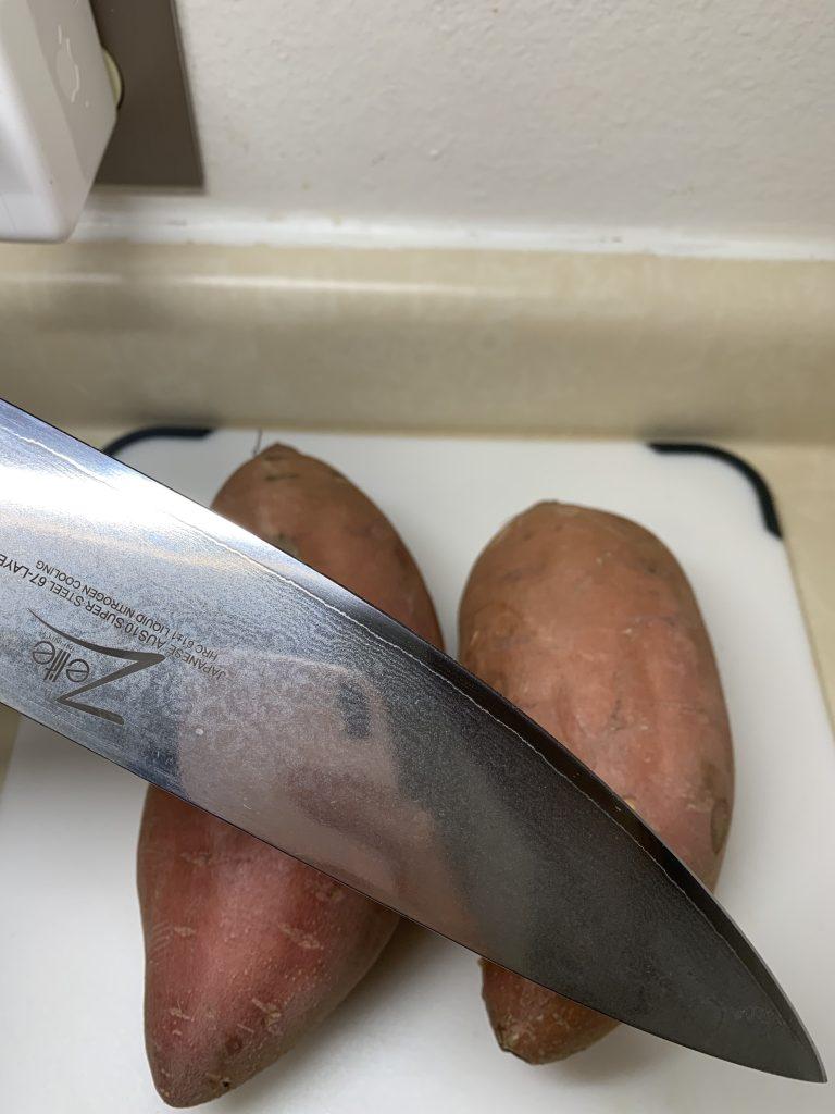 A big knife and two jewel yams on a cutting board