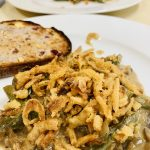 vegan green bean casserole on a white plate with bread