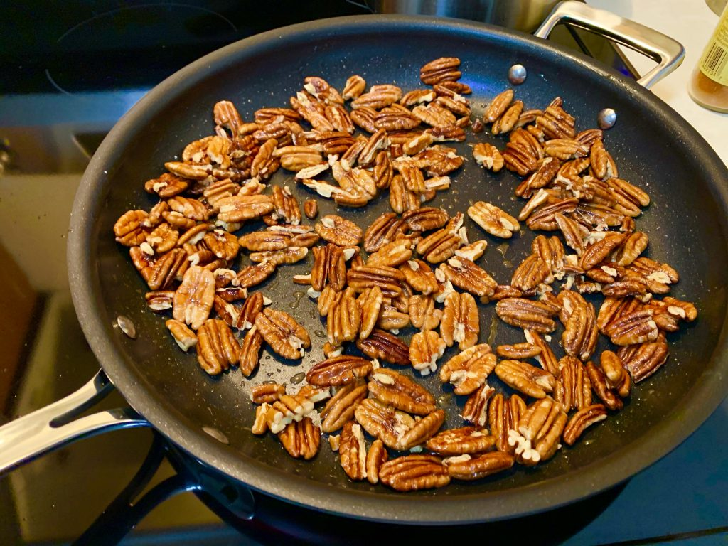Toasted, caramelized maple pecans in a non-stick pan