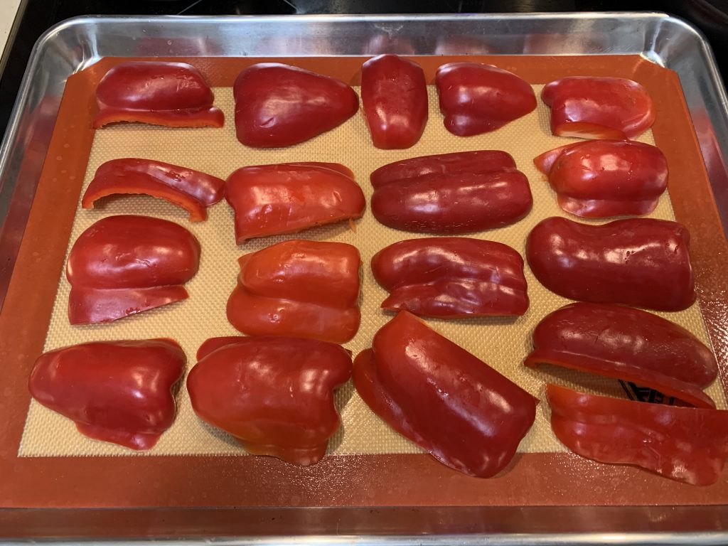 Roasted red peppers cut and ready to roast in the oven, on a pan on a sil-mat