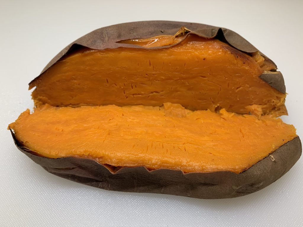 orange Jewel yam, baked and sliced in half with a white background
