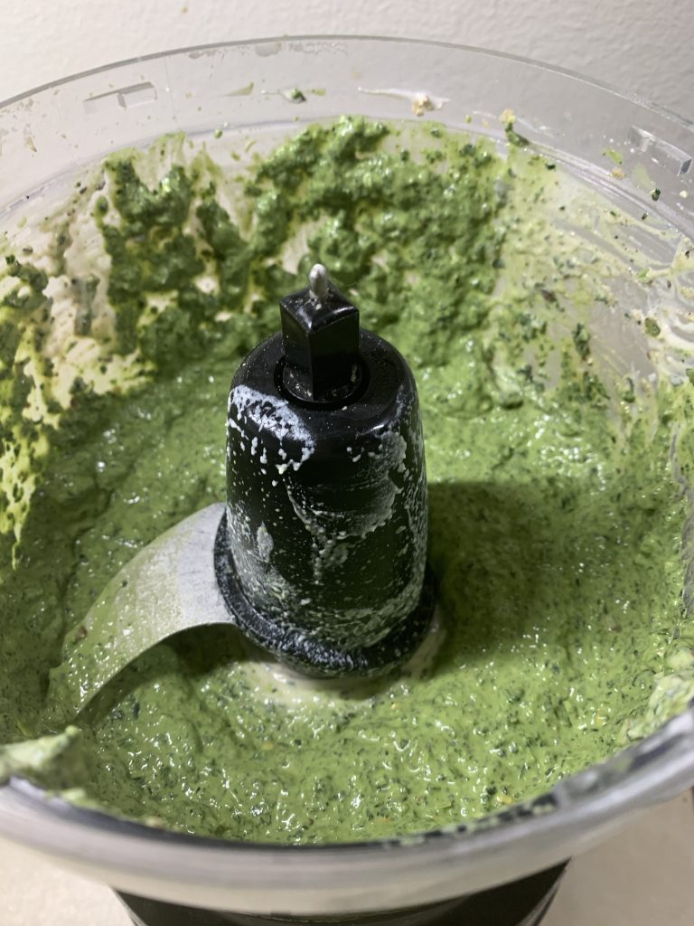 Adding the cashew cream and processing into a lighter green pesto looking mixture.