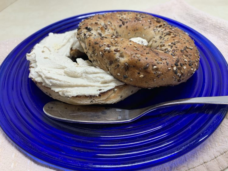 An Everything Bagel with Vegan Cashew Cream Cheese on a blue plate