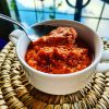 Red romesco sauce in a white saucer