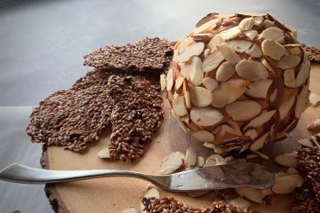 Vegan Yippee-Ki-Yay Holiday Vegan Cheese Ball on wod with almonds and flaxseed crackers