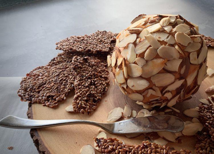 Vegan Yippee-Ki-Yay Holiday Vegan Cheese Ball on wod with almonds and flaxseed crackers