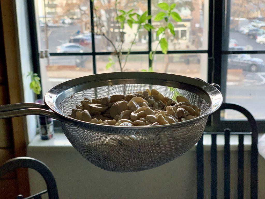 Draining boiled cashews