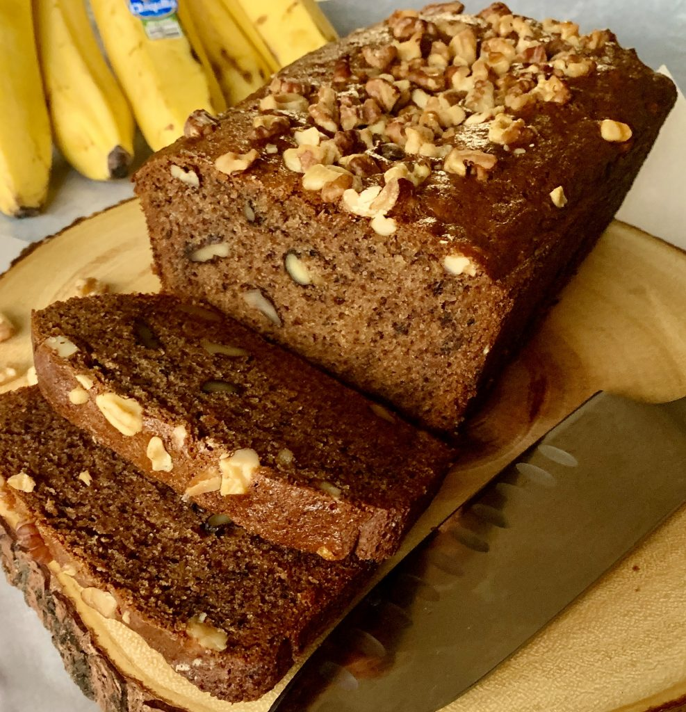Sliced vegan banana bread on a wooden cutting board with a large knife.