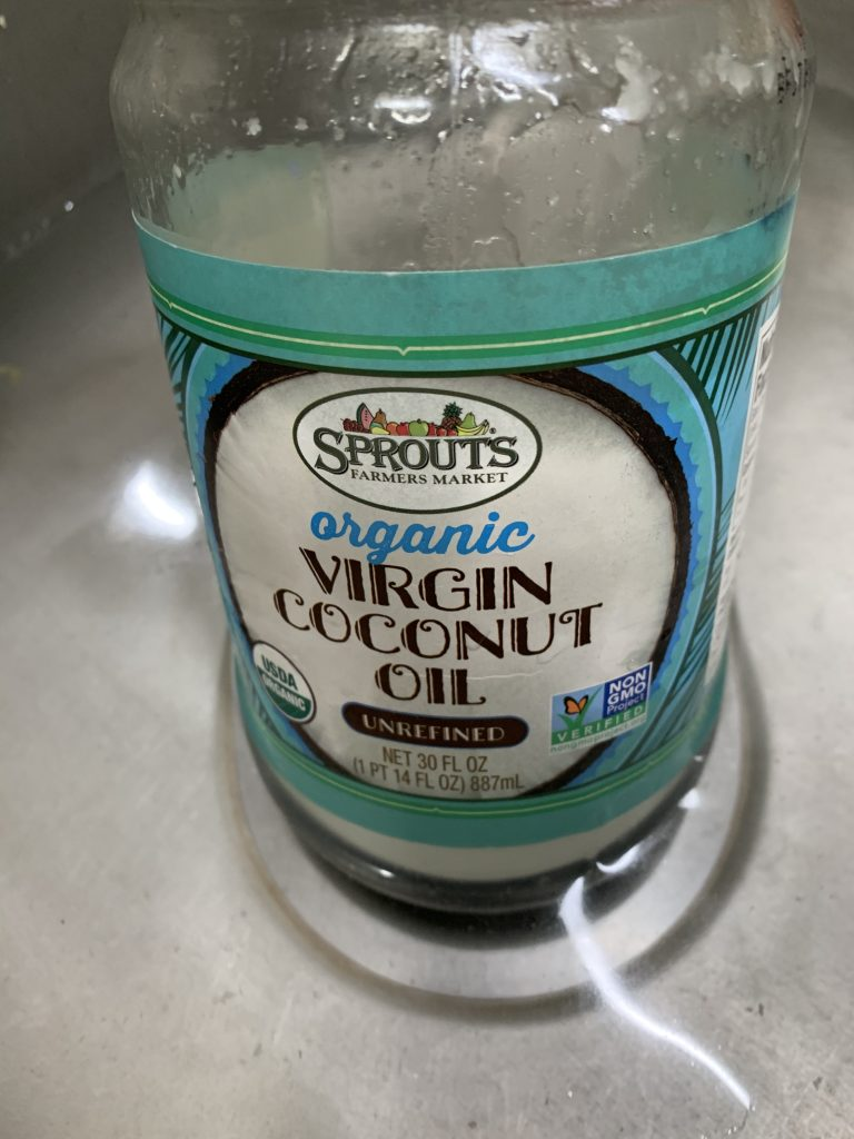 A jar of Virgin Coconut Oil in a hot water bath to liquify