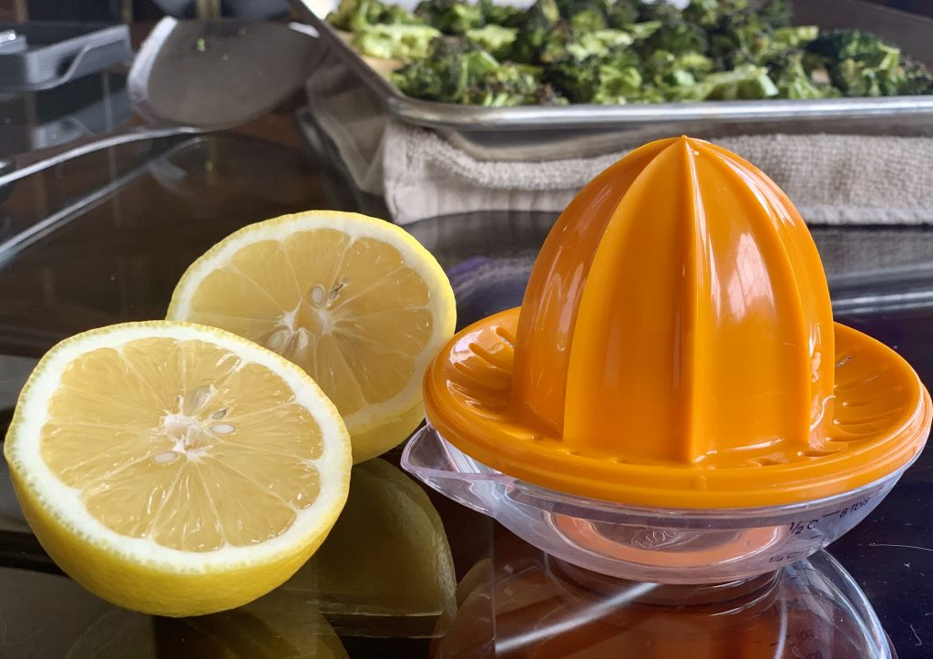 Lemon cut half ready to juice next to the juicer with broccoli in the background.