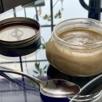 a jar homemade tahini on a glass table with a spoon