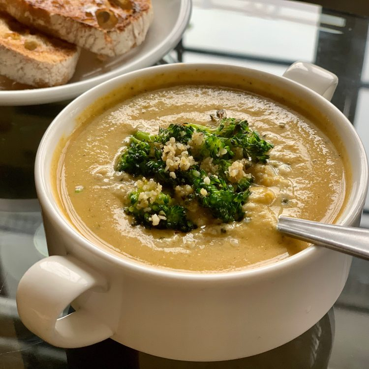 Vegan Broccoli Cheese soup in a white cup with toast
