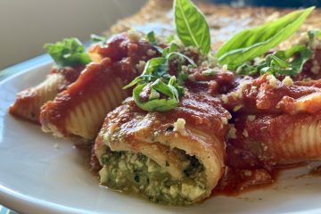 Vegan ricotta stuffed shells on a white plate with red sauce and garlic shake hempseed parm