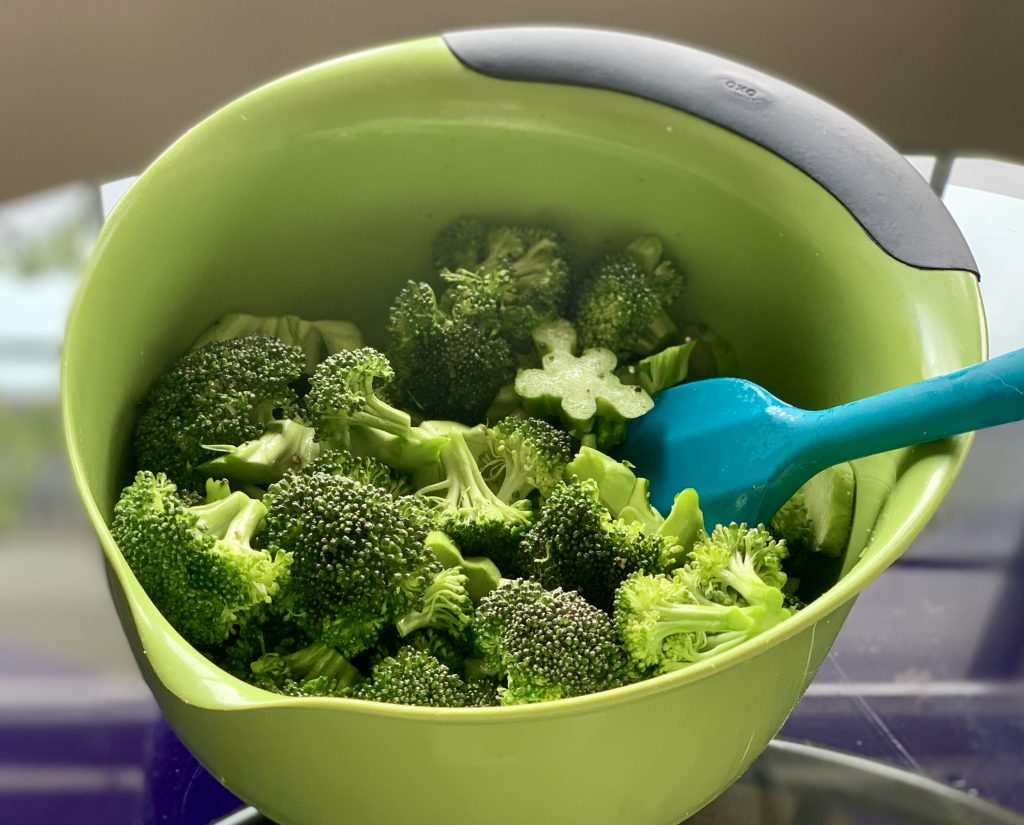 Stirring the broccoli to coat it with olive oil. By Plant Test Kitchen