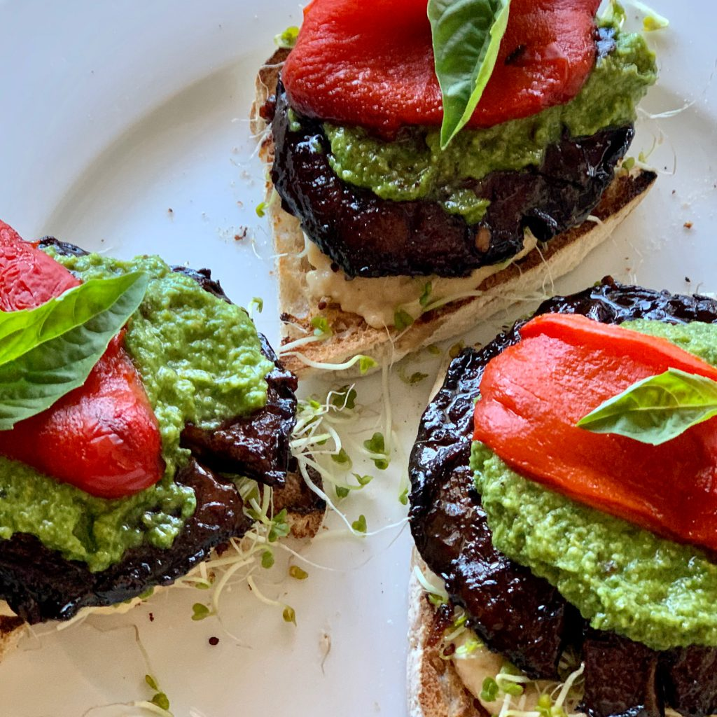 Easy Oven-Roasted Marinated Portobellos served with Zesty Avocado Pistachio Pesto, roasted red peppers, Aquafaba low-oil hummus, sprouts, and grilled bread. By Plant Test Kitchen.