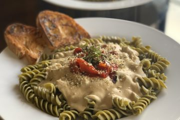 Vegan Alfredo on rotini green pasta wit red peppers and garlic shake on a white plate