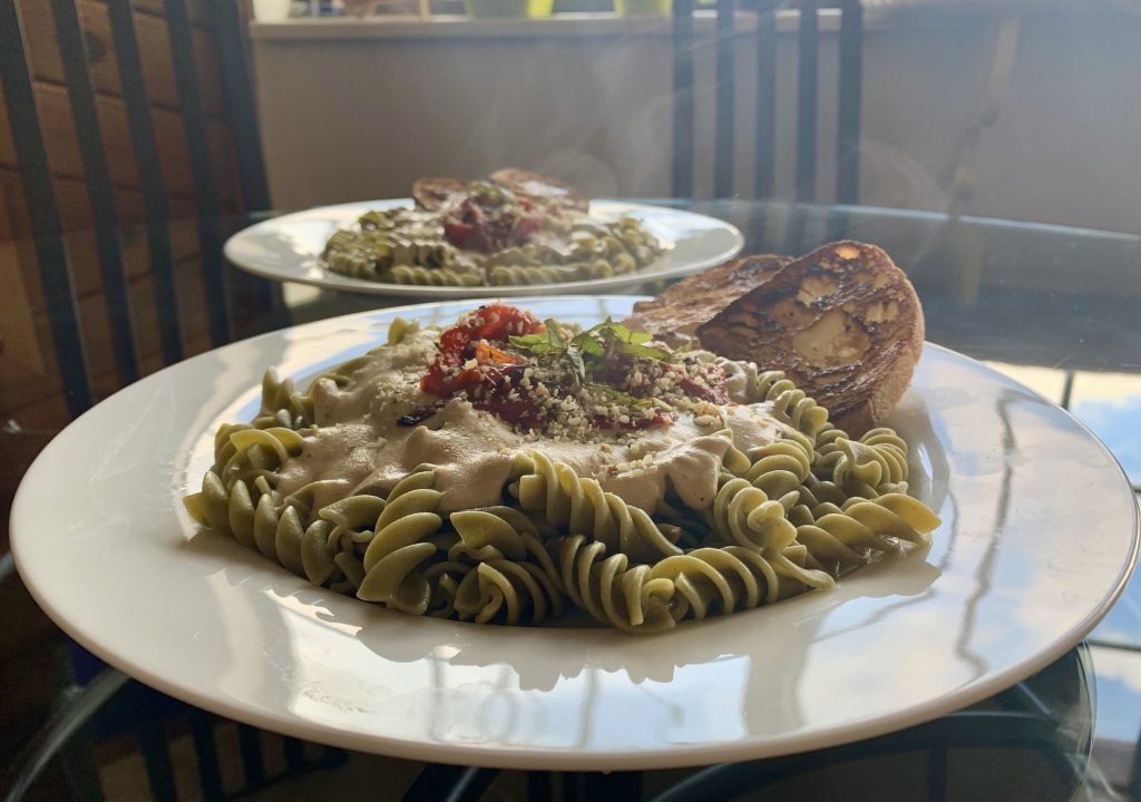 Vegan Garlic Alfredo Sauce over green pasta with garlic hempseed parm on a white plate with red peppers and bread