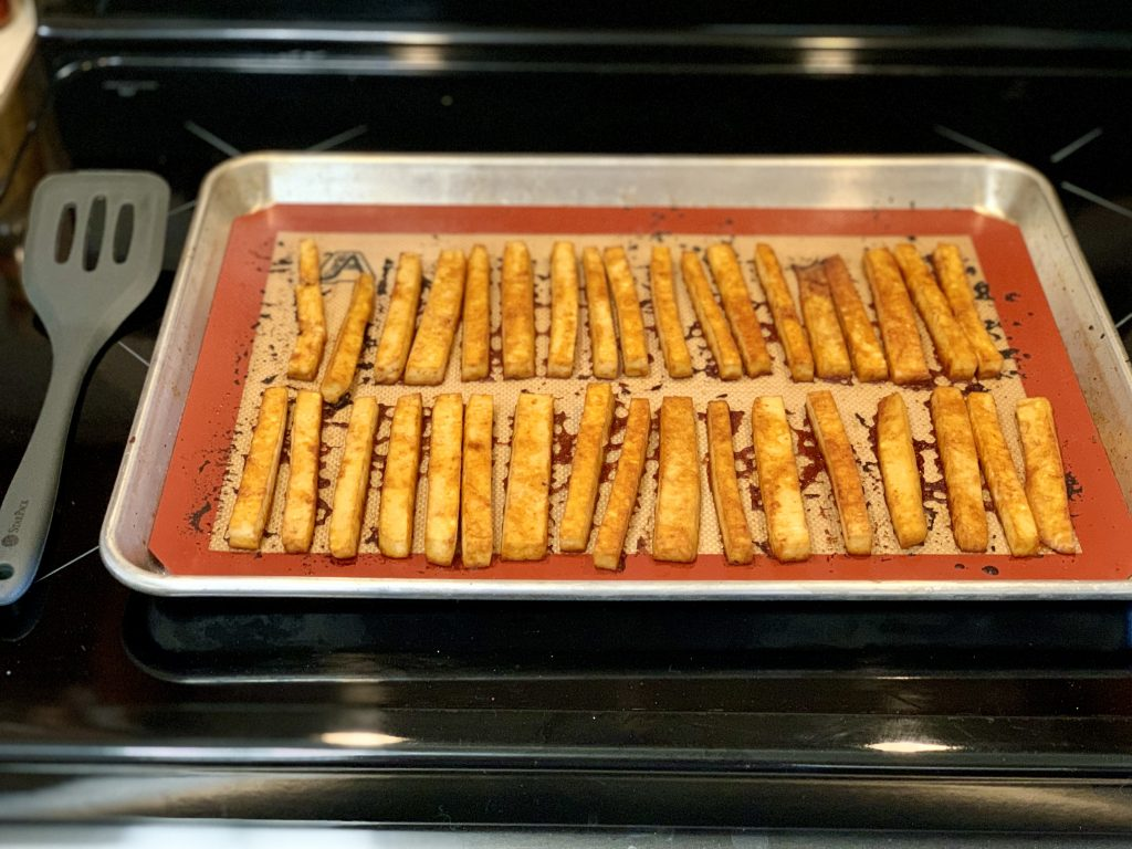 tofu out of the oven, ready to flip, brush remaining sauce on, and return to the oven