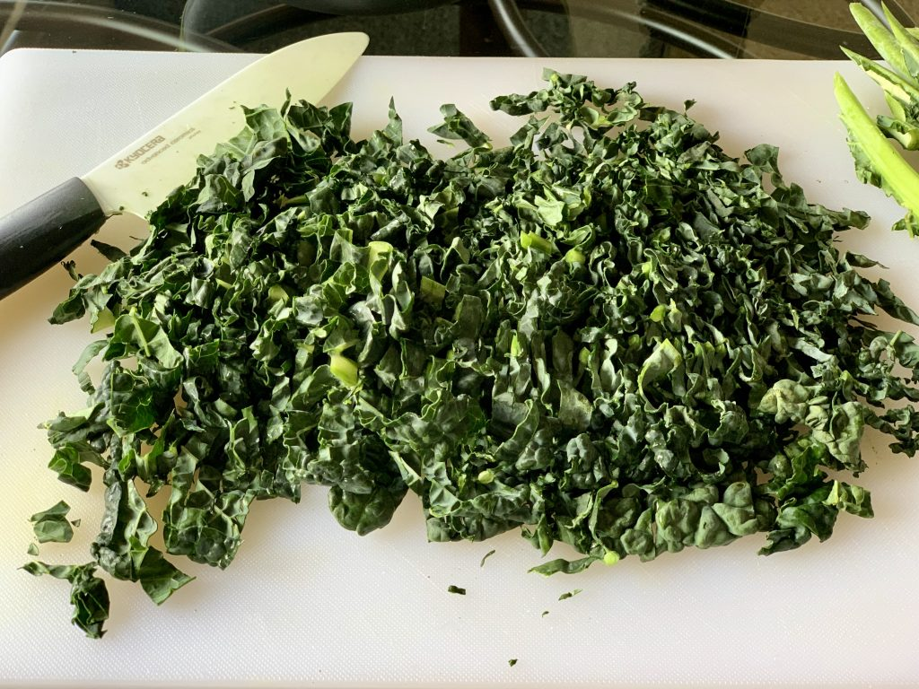 Dino Kale sliced into ribbons on a white cutting board