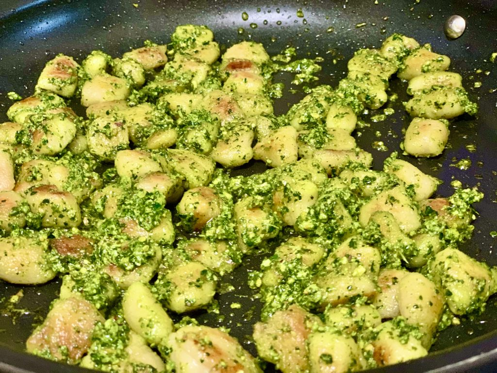 Tossing gnocchi with pesto in the pan