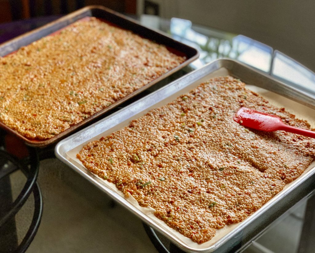 Spreading Rosemary Oven-Baked Sun-Dried Tomato Whole Flaxseed Crackers a.k.a. Flackers onto lined baking sheets