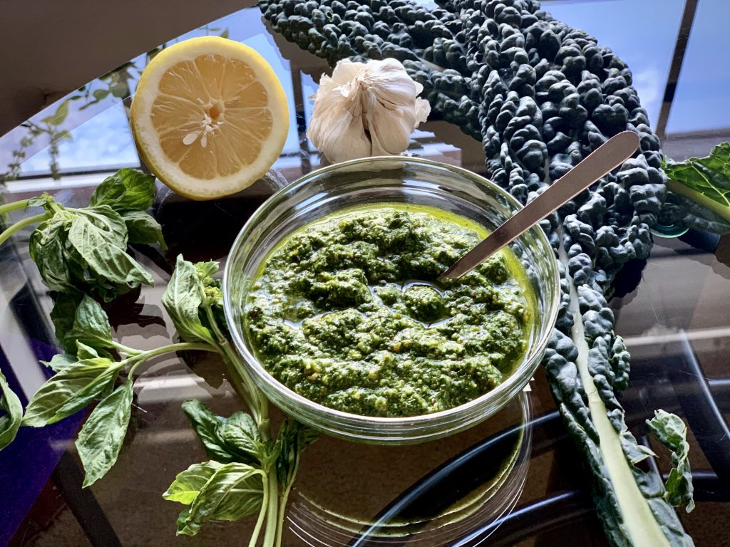 Lemon Kale-Basil Pesto in a glass bowl with basil, lemon, garlic and kale