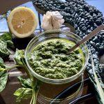 Lemon Kale-Basil Pesto in a glass bowl with basil, lemon, garlic and kale