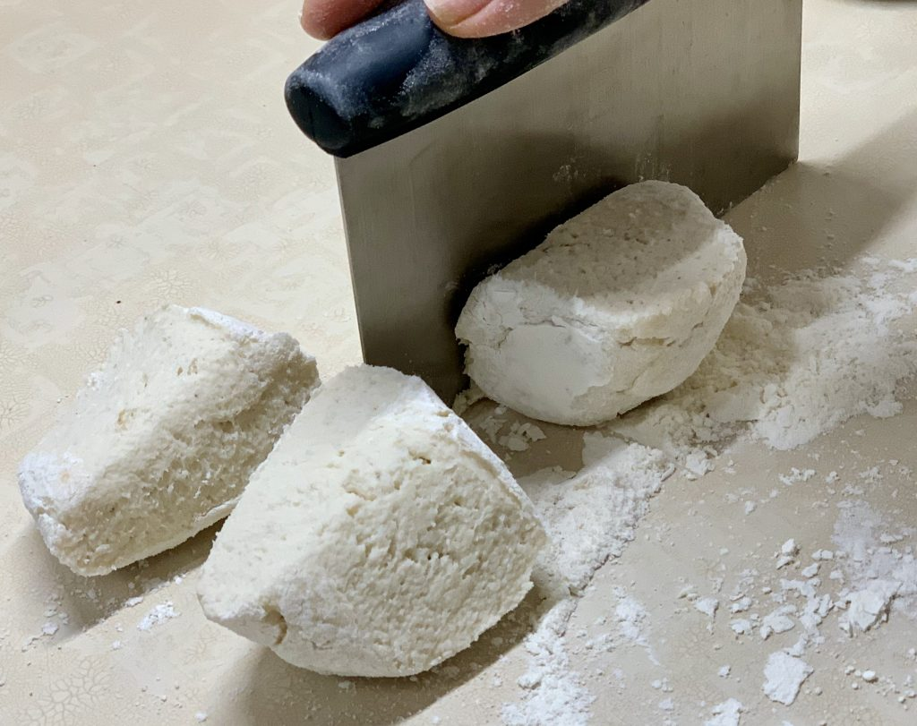 Cutting the halves of caulifloer gnocchi dough in half