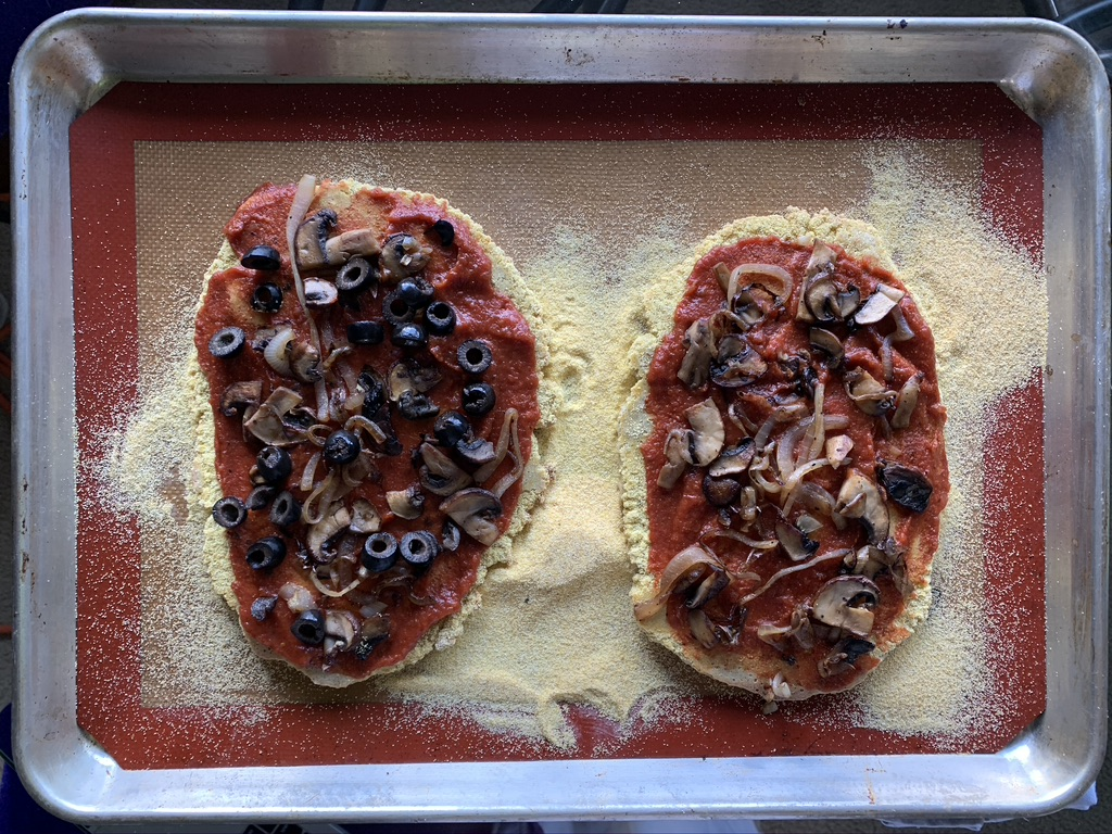 Sauced quinoa pizza crust with toppings on a sil-mat