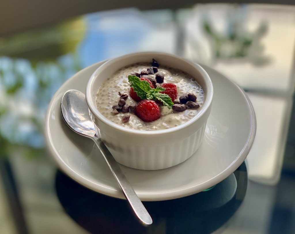 Banana Coconut Chia Pudding topped with raspberries, cacao nibs, and mint leaves.