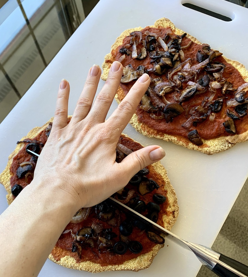 Pressing down on a big Paul Hogan-approved knife to cut personal pizzas with quinoa flatbread