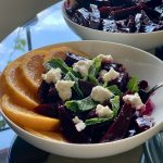 Orange-Rosemary Glazed Beets plated with orange slices mint leaves and macadamia ricotta