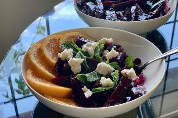 Orange-Rosemary Glazed Beets plated with orange slices mint leaves and macadamia ricotta