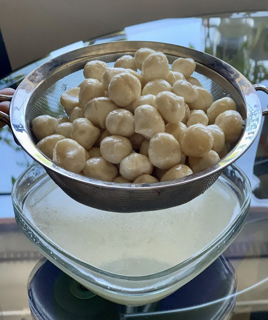Draining the macadamia nuts and saving the soaking liquid