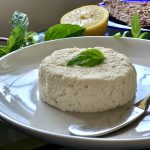 Vegan Macadamia Nut Ricotta on a white plate topped with a basil leaf
