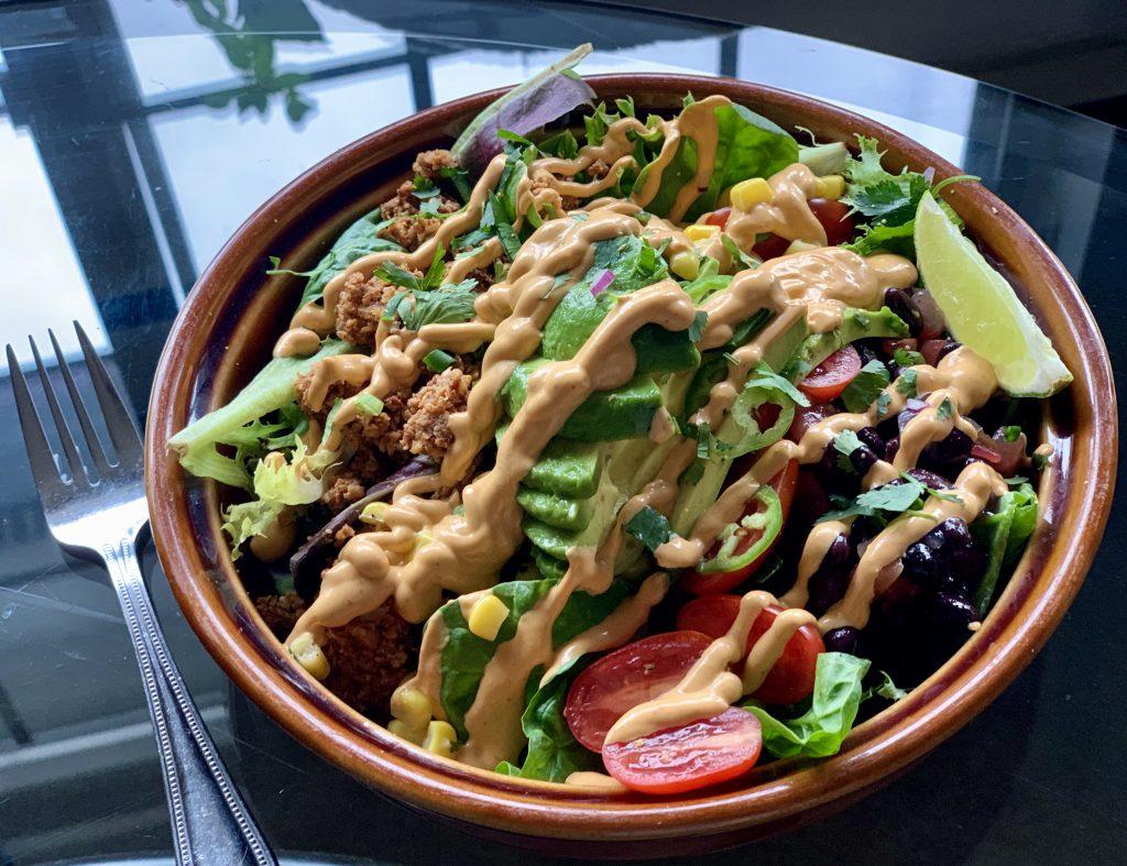 Easy Vegan Nacho Cheese Queso on a burrito bowl