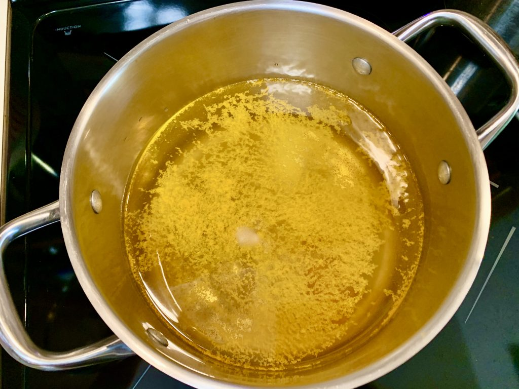 Bringing water, salt, and turmeric to a boil in a large pot