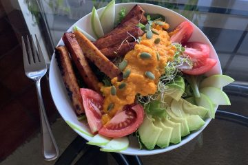 Carrot Ginger Miso Dressing on a salad with avocado, sprouts sriracha tofu, tomatoes and pumpkin seeds in a white bowl on a glass table