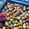 Crispy Roasted Vegan Garlic Potatoes on a roasting sheet with ketchup