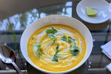 Orange colored Vegan curried coconut carrot soup topped with green cliantro leaves swirled with coconut milk in a white bowl on a glass table with a spoon and small white plate with a wedge of lime next to it.