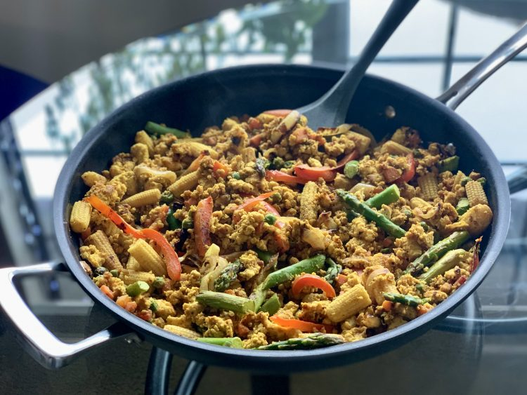 Vegan Veggie Tofu Scramble in a skillet on a glass table