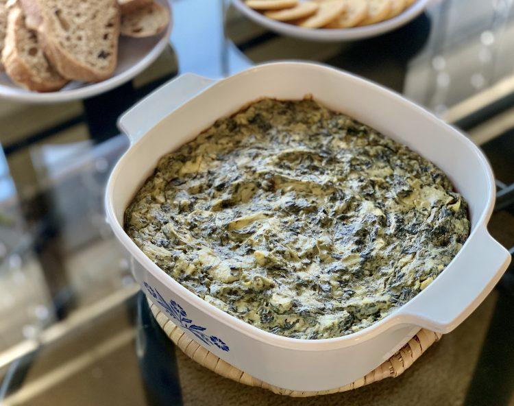 vegan spinach & artichoke dip in a white square casserole dish