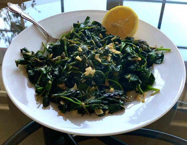 Lemon Garlic Sautéed Spinach on a white plate on a glass table