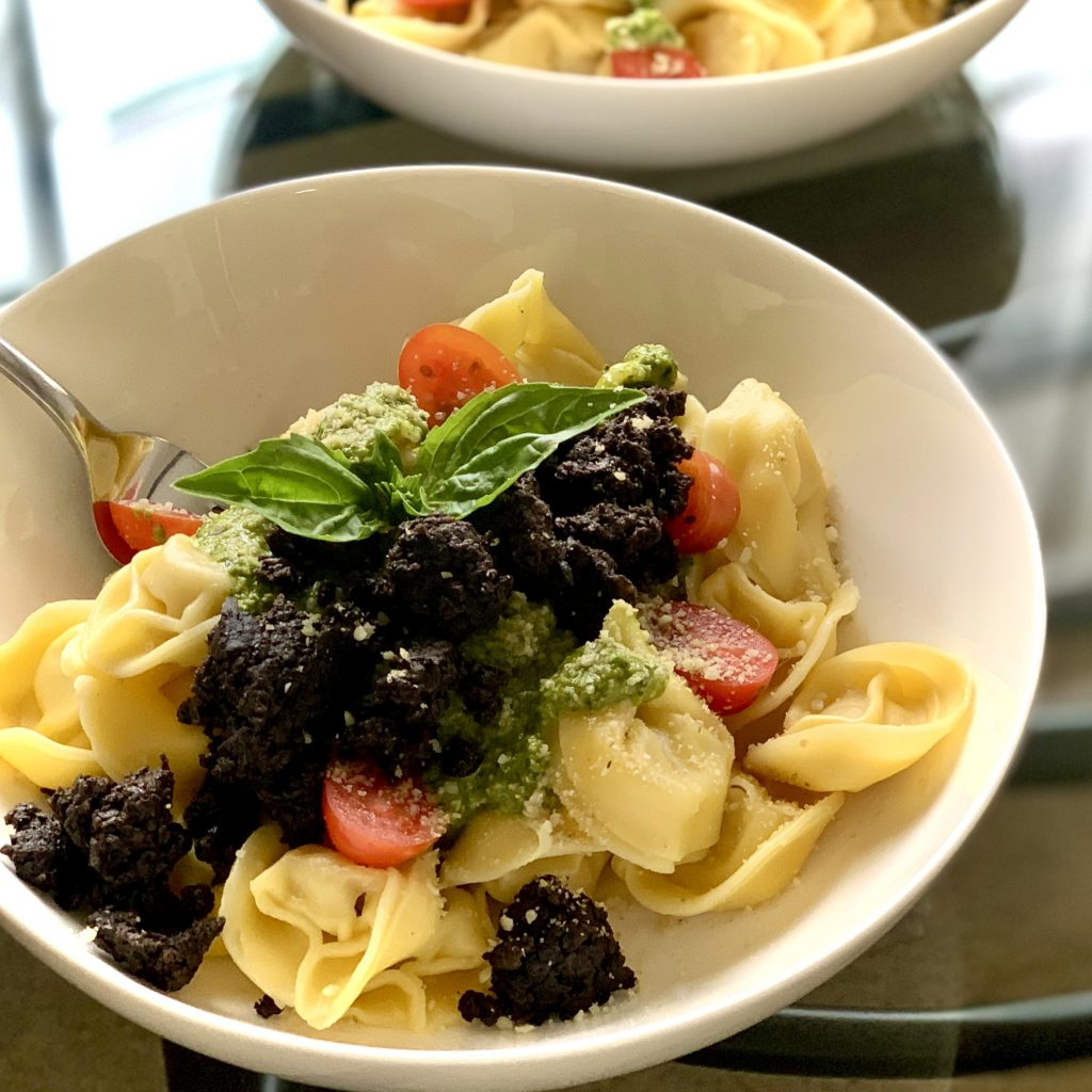 Easy Seasoned Mushroom Mince over Vegan Kite Hill Almond Ricotta Tortellini with Cilantro Pumpkin Seed Pesto & grape tomatoes, dusted with 5-Minute Garlic Hemp Seed Parm a.k.a. Garlic Shake