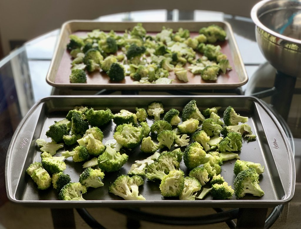 Broccoli divided on two baking sheets ready to become Roasted Broccoli with Vegan Garlic Parm