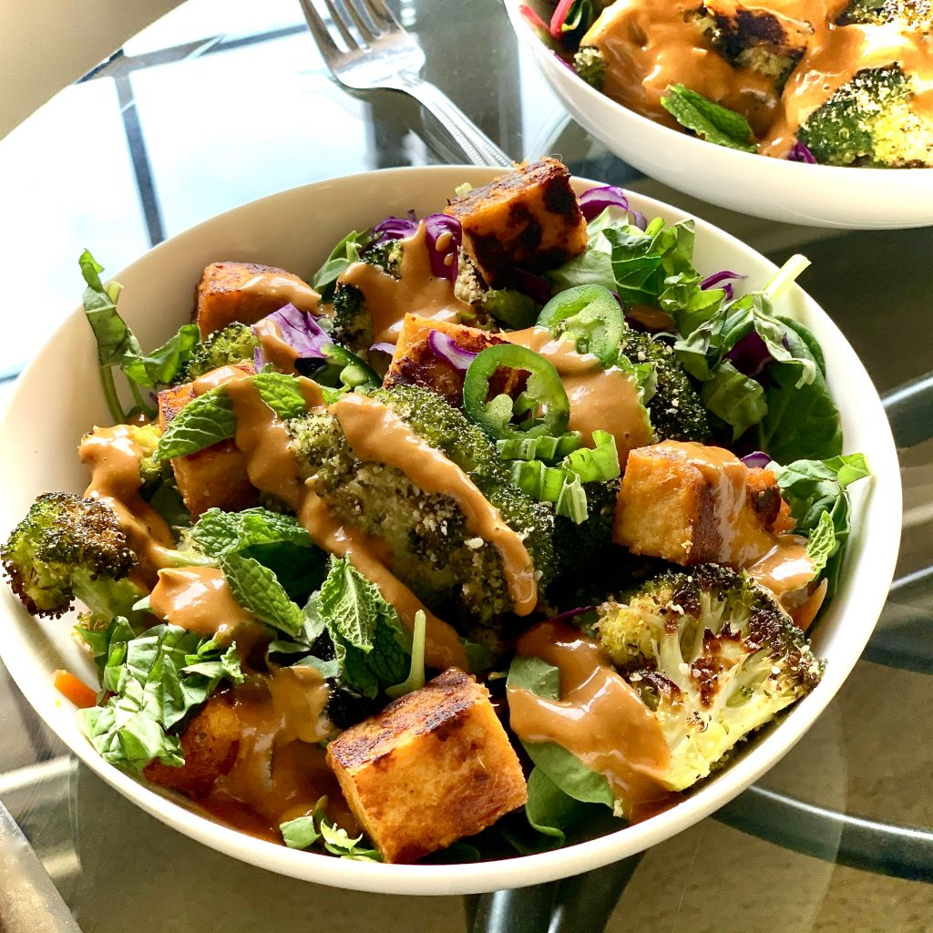 Roasted Broccoli with Vegan Garlic Parm in a bowl with Miso Tofu, mint leaves, mixed greens and Thai Basil, topped with Crazy Good No-Peanut Sauce